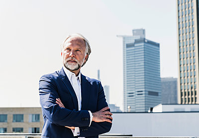 Serious mature businessman in the city looking around - p300m1587417 von Uwe Umstätter