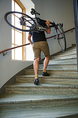 Sweden, Cyclist carrying bicycle on steps - p352m1350190 by Folio Images