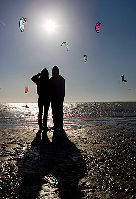 Couple watching kite boarders - p4296895f by Nick Dolding