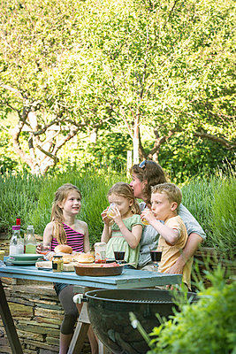 Family eating together at table outdoors - p429m696641 by Zac Macaulay