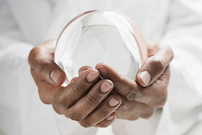 Close up of mixed race man holding crystal ball - p555m1478183 by REB Images