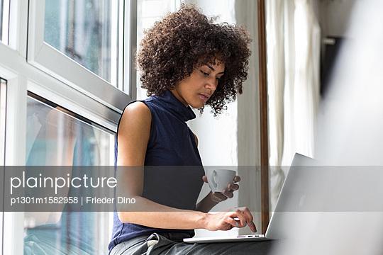 Geschäftsfrau sitzt mit ihrem Laptop auf einer Fensterbank  - p1301m1582958 von Delia Baum