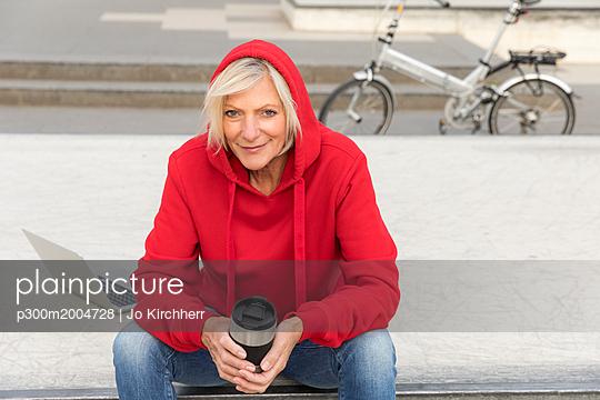 Senior woman wearing red hoodie sitting outdoors with laptop and takeaway coffee - p300m2004728 von Jo Kirchherr