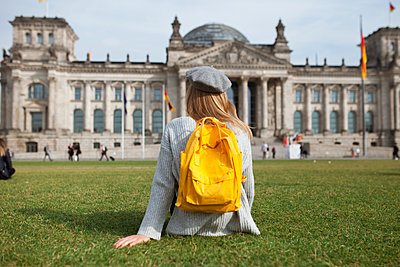 Young woman sitting in park by Reichstag in Berlin, Germany - p1427m2110230 by Mykhailo Lukashuk