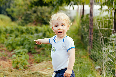 Toddler pointing at something in vegetable garden - p300m911363f by Mareen Fischinger