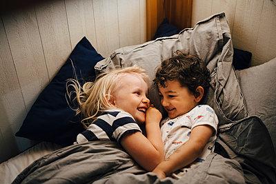 Smiling siblings sleeping in bedroom at night - p426m2259487 by Maskot