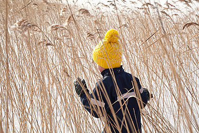 Boy walking through long grass, in snow covered landscape, rear view - p924m1422674 by Tiina & Geir