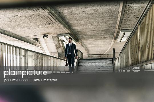 Businessman walking at underpass - p300m2005330 von Uwe Umstätter