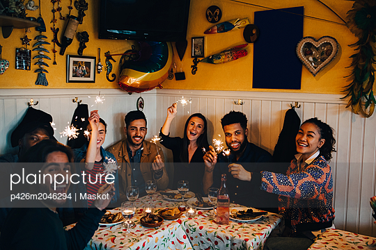 Portrait of cheerful young multi-ethnic friends sitting with sparklers at table in restaurant - p426m2046294 by Maskot