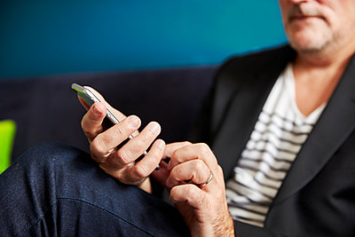 Close up of a man using his mobile phone. - p1100m1177695 by Mint Images