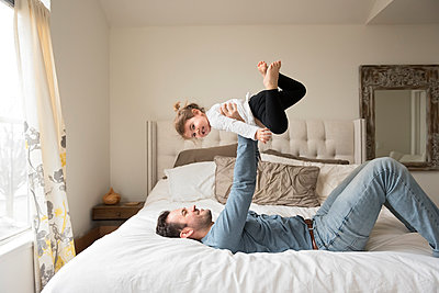Playful father lifting daughter while on bed at home - p1166m1568980 by Cavan Images