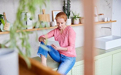 Beautiful woman using digital tablet while sitting on countertop at home - p300m2265231 by Jo Kirchherr