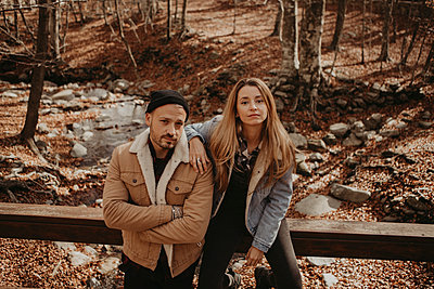 Hipster man standing by girlfriend sitting on wooden railing at forest during autumn - p300m2274818 by Gala Martínez López