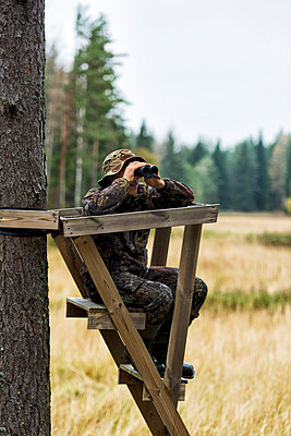 Teenager with binoculars on hunting tower - p312m798841 by Hans Berggren