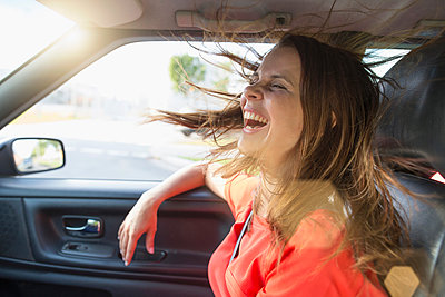Mid adult woman with flyaway hair in front seat of car - p429m1408027 by Philipp Nemenz