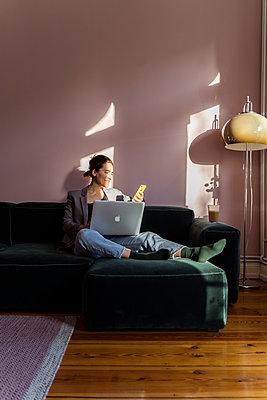 Gut gelaunte Frau im Home Office - p432m2172093 von mia takahara