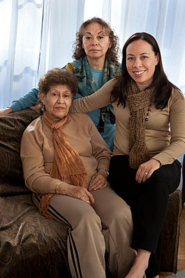 Three generations of women smiling on sofa - p555m1408858 by Shestock