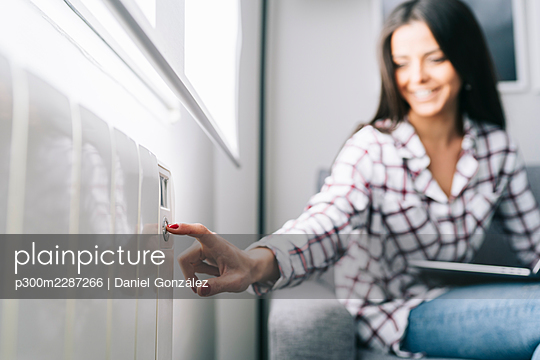Young woman touching heating push button at home - p300m2287266 by Daniel González