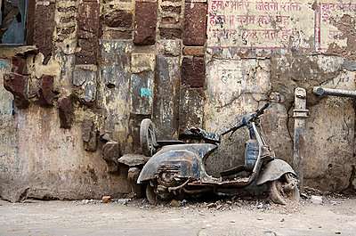 Defunct motorscooter leaning against derelict city wall - p1072m941368 by chinch gryniewicz