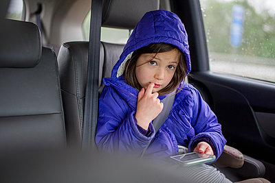 A little girl in the backseat of a car glances up from a phone - p1166m2165931 by Cavan Images