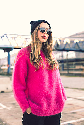 Portrait of fashionable young woman wearing sunglasses, cap and pink knit pullover - p300m2078656 by Aitor Carrera Porté