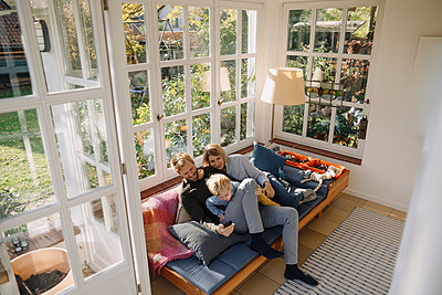 Family using cell phone in sunroom at home - p300m2205536 by Kniel Synnatzschke