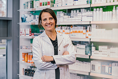 Confident female pharmacist with arms crossed in chemist shop - p300m2243117 by Mareen Fischinger