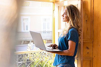 Thoughtful woman with laptop looking through window at home - p300m2256591 by Steve Brookland