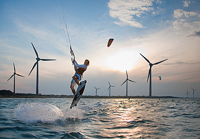 Croatia, Zadar, Kitesurfer jumping in front of wind turbine - p300m980477f by hsimages