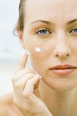 Woman applying sunscreen to face - p62310289f by Rafal Strzechowski