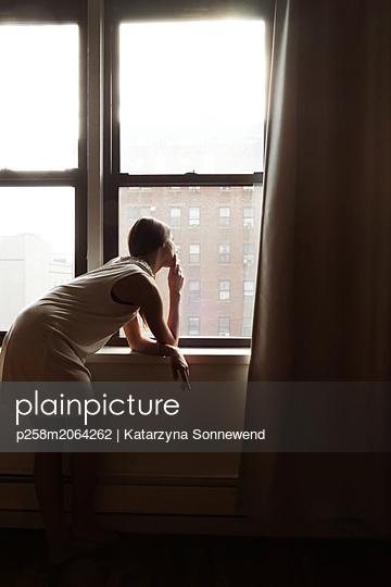 Woman at window - p258m2064262 von Katarzyna Sonnewend