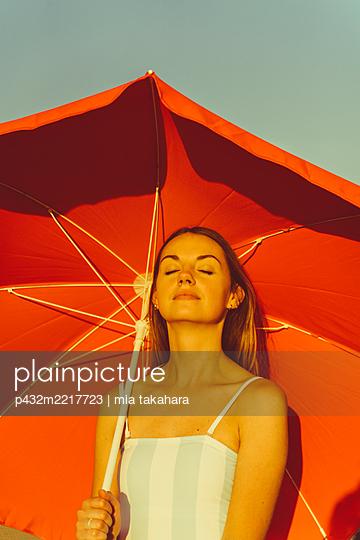 Junge Frau sonnt sich unter Sonnenschirm - p432m2217723 von mia takahara
