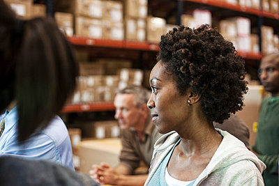 African American female warehouse worker with team of multi-ethnic workers in a large warehouse distribution centre. - p1100m1575472 by Mint Images