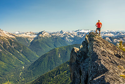 Climber stands on the summit of a rocky mountain peak, B.C. Canada - p1166m2212398 by Cavan Images