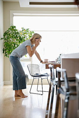 Woman working from home, talking on smart phone at laptop in dining room - p1192m2088348 by Hero Images