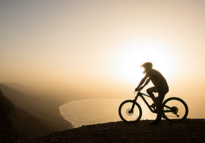 Spain, Lanzarote, mountainbiker on a trip at the coast at sunset - p300m2102593 by Hernandez and Sorokina