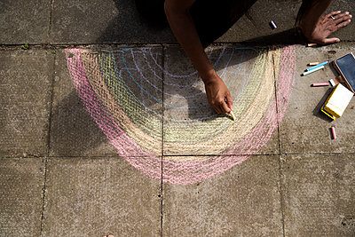 Arms of adult woman drawing crayon rainbow on pavement - p300m2243278 by Pete Muller
