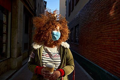 Brown curly hair woman wearing protective face mask looking away while standing with coffee cup on footpath - p300m2256710 by Veam