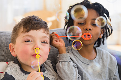 Close up of boys blowing bubbles on sofa - p555m1410963 by JGI/Jamie Grill