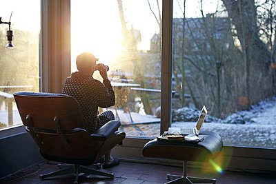 Woman sitting in living room and watching her garden with binoculars - p896m1479444 by Richard Brocken