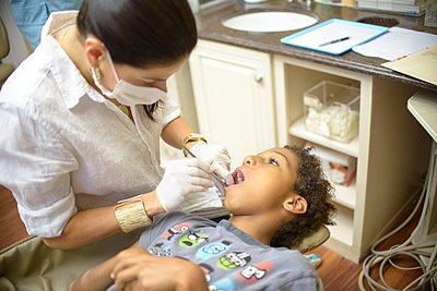 Female orthodontist examining boy in dental surgery - p924m1054052f by Sue Barr