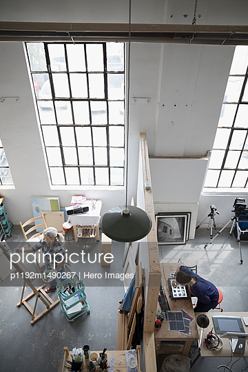 Female painter painting at canvas and photographer reviewing photographic slides in coworking space art studio - p1192m1490267 by Hero Images