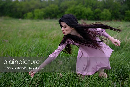 Junge Frau pflückt im Wind Blumen - p1646m2289340 von Slava Chistyakov