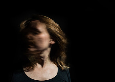Close-up of woman shaking head while standing against black background - p1166m2024656 by Cavan Images