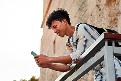 Young man with afro hair is using his smartphone outdoors - p1166m2201852 by Cavan Images