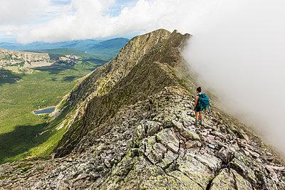 Teenage girl hiking along mountain ridge at Knife Edge Trail on Mount Katahdin in Baxter State Park, Maine, USA - p1424m1579459 by Jerry Monkman