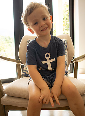 Blond boy sitting on a chair - p1640m2254817 by Holly & John