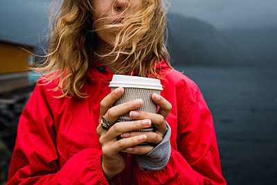 Norway, Lofoten, close-up of young woman at the coast holding takeaway coffee - p300m2042271 by Kike Arnaiz