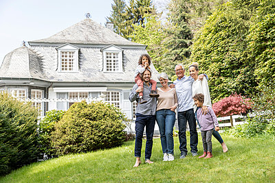 Happy extended family standing in garden of their home - p300m2132349 by MiJo