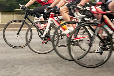Waist down view of group of racing cyclists speeding on urban road in racing cycle race - p429m1118574f by Seb Oliver